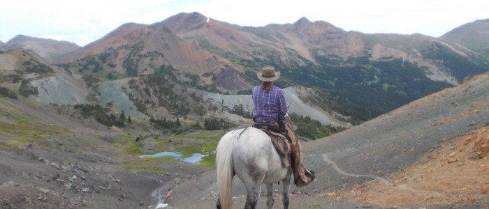 Riding through the mountains as a pack trip guide